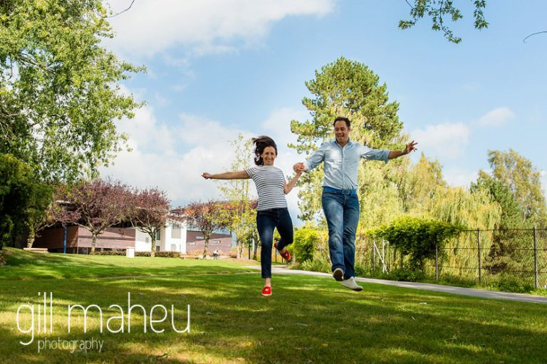 engaged couplerunning towards camera in park on Divonne, Geneva engagement session by Gill Maheu Photography, photographe de mariage
