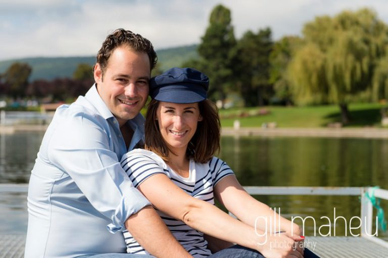 engaged couple sitting in front of the lake on Divonne, Geneva engagement session by Gill Maheu Photography, photographe de mariage