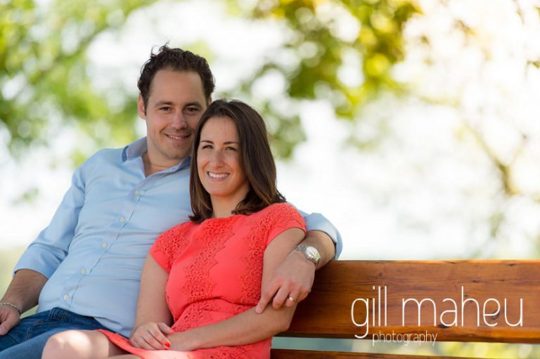 engaged couple embracing on bench at Divonne, Geneva engagement session by Gill Maheu Photography, photographe de mariage