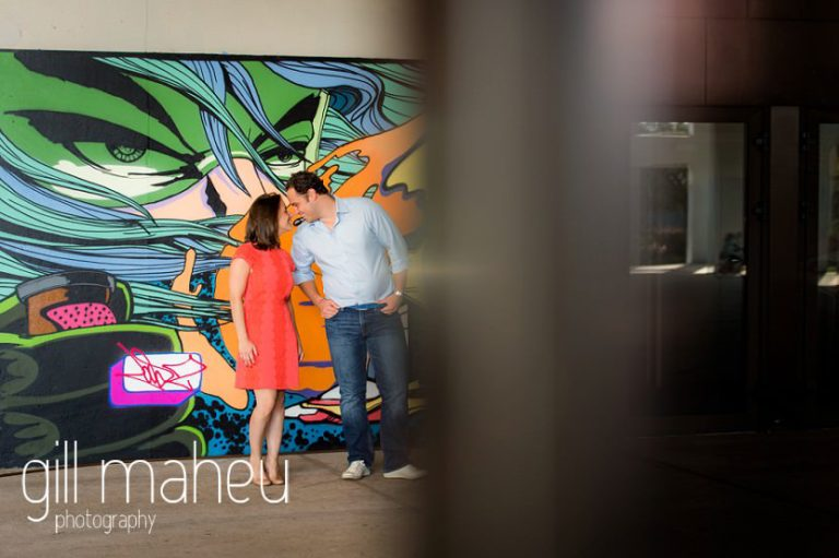 engaged couple kissing in front of graffitti wall on Divonne, Geneva engagement session by Gill Maheu Photography, photographe de mariage