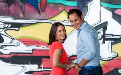 engaged couple laughing in front of colourful graffitti wall at Divonne, Geneva engagement session by Gill Maheu Photography, photographe de mariage