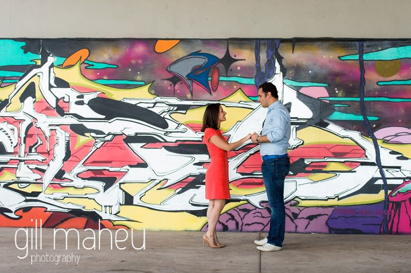 engaged couple holding hands in front of graffitti wall on Divonne, Geneva engagement session by Gill Maheu Photography, photographe de mariage