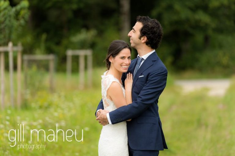 portrait of bride in Monique l'huillier lace wedding dress and groom embracing in a field of golden flowers on Geneva love the dress day after session by Gill Maheu Photography, photographe de mariage
