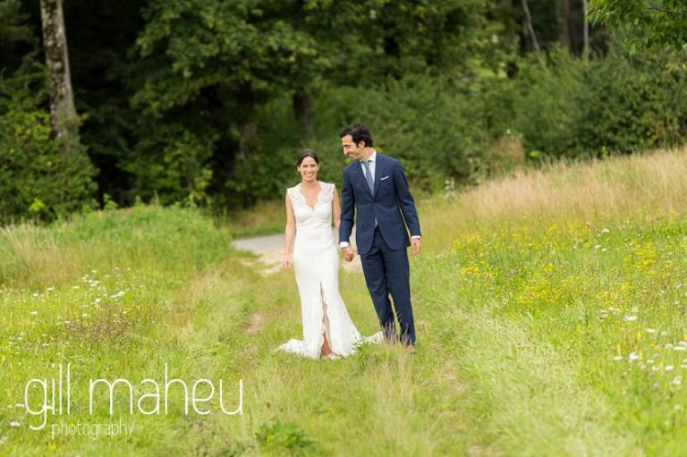 portrait of bride in Monique l'huillier lace wedding dress and groom walking towards camera in a field of golden flowers on Geneva love the dress day after session by Gill Maheu Photography, photographe de mariage