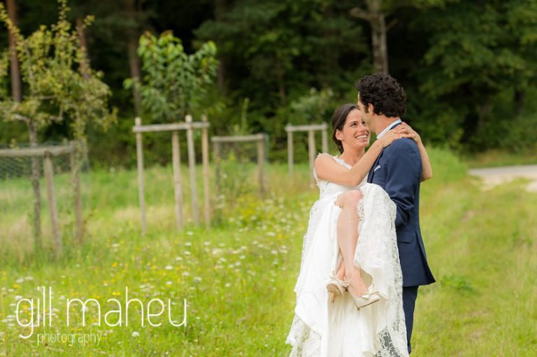 bride in groom's arms in a field of golden flowers on Geneva love the dress day after session by Gill Maheu Photography, photographe de mariage