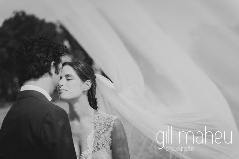 black and white photo of bride in Monique l'huillier wedding dress and fabulous cathedral veil smiling up at groom on Geneva love the dress day after session by Gill Maheu Photography, photographe de mariage