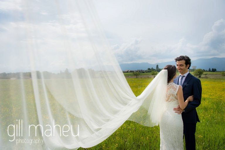 artistic photo of cathedral veil with bride in Monique l'huillier wedding dress and groom in background on Geneva love the dress day after session by Gill Maheu Photography, photographe de mariage