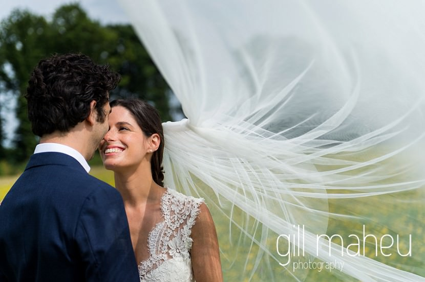 romantic photo of bride in Monique l'huillier wedding dress and fabulous cathedral veil smiling up at groom on Geneva love the dress day after session by Gill Maheu Photography, photographe de mariage