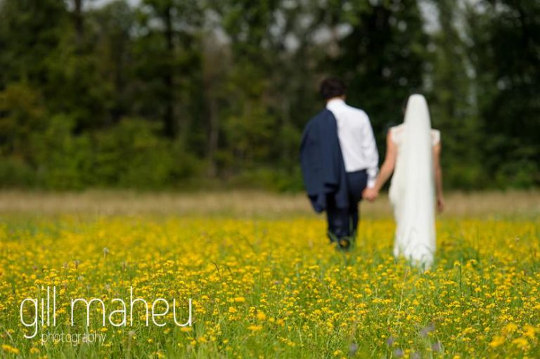 bride and groom walking away from camera in a field of golden flowers on Geneva love the dress day after session by Gill Maheu Photography, photographe de mariage
