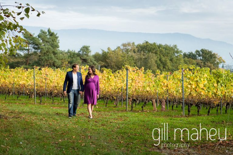 future parents walking through vineyards in maternity session in Collonges, Geneva, by Gill Maheu Photography, photographe de Grossesse et lifestyle