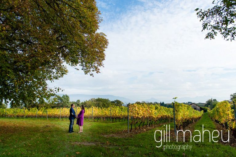 wide angle of future parents walking through vineyards in maternity session in Collonges, Geneva, by Gill Maheu Photography, photographe de Grossesse et lifestyle