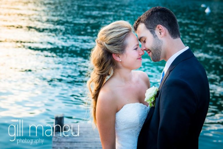 close up romantic photo of bride and groom kissing on the ponton jetty at Abbaye de Talloires, Lake Annecy wedding by Gill Maheu Photography, photographe de mariage