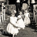 black and white photo of adorable little flower girls walking down aisle at Abbaye de Talloires, Lake Annecy wedding by Gill Maheu Photography, photographe de mariage
