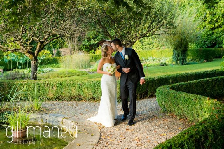 bride and groom kissing in the gardens of Abbaye de Talloires, Lake Annecy wedding by Gill Maheu Photography, photographe de mariage