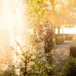 bride and groom in setting sun in the gardens of Abbaye de Talloires, Lake Annecy wedding by Gill Maheu Photography, photographe de mariage