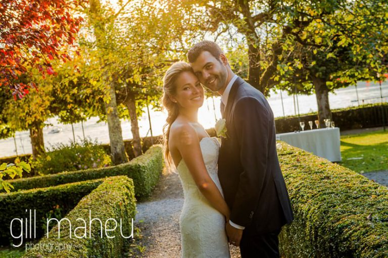 portrait of bride and groom looking at the camera taken against the sun in the gardens of Abbaye de Talloires, Lake Annecy wedding by Gill Maheu Photography, photographe de mariage