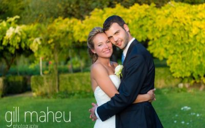 romantic couple portrait of bride and groom smiling at the camera in golden sunlight in gardens of Abbaye de Talloires, Annecy wedding by Gill Maheu Photography, photographe de mariage