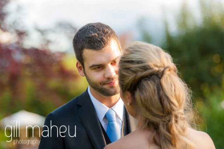 close up of groom looking lovingly at bride in sunlit gardens of Abbaye de Talloires, Annecy wedding by Gill Maheu Photography, photographe de mariage