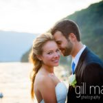 romantic close up shot of bride looking at the camera whilst groom whispers in her ear at Abbaye de Talloires, Annecy wedding by Gill Maheu Photography, photographe de mariage