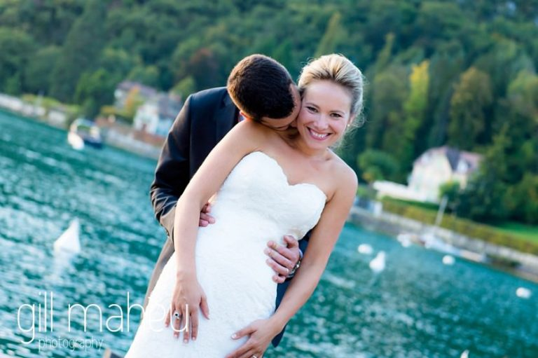 groom kissing giggling bride's shoulder in front of turquoise lake at Abbaye de Talloires, Annecy wedding by Gill Maheu Photography, photographe de mariage