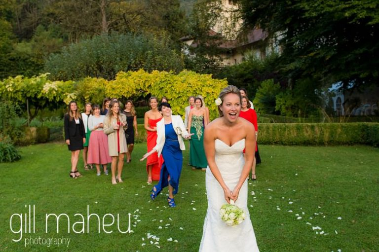 bride throwing her wedding bouquet at Abbaye de Talloires, Lake Annecy wedding by Gill Maheu Photography, photographe de mariage