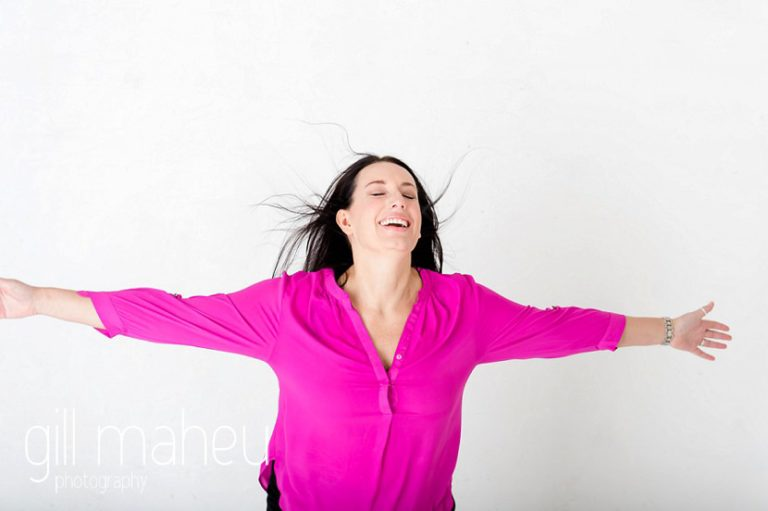 laughing at bright coloured natural relaxed headshot and branding photography session in white studio for young woman entrepreneur by Gill Maheu Photography, photographe de headshot et portrait