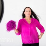 striking a pose with pompoms at bright coloured natural relaxed headshot and branding photography session in white studio for young woman entrepreneur by Gill Maheu Photography, photographe de headshot et portrait