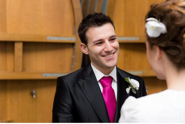 groom smiling at his bride in front of huge vat in wine cellar at Lausanne wedding by Gill Maheu Photography, photographe de mariage