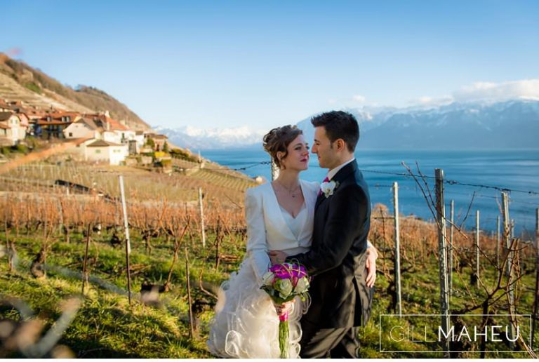 portrait of bride and groom outside in spring sunshine kissing in front of view of Lac Léman at Lausanne wedding by Gill Maheu Photography, photographe de mariage