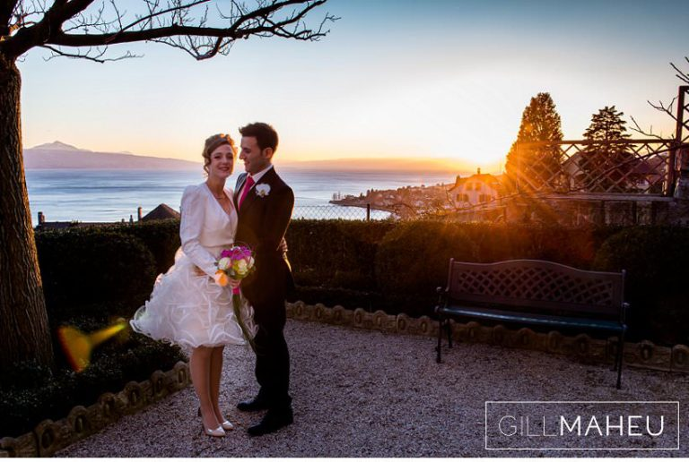 bride and groom embracing in front of sunset over Lac Léman at Lausanne wedding by Gill Maheu Photography, photographe de mariage