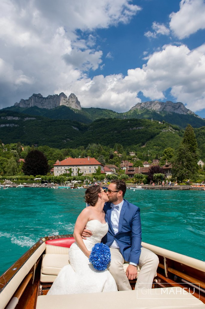 bride and groom kissing on boat with abbaye de talloires in background