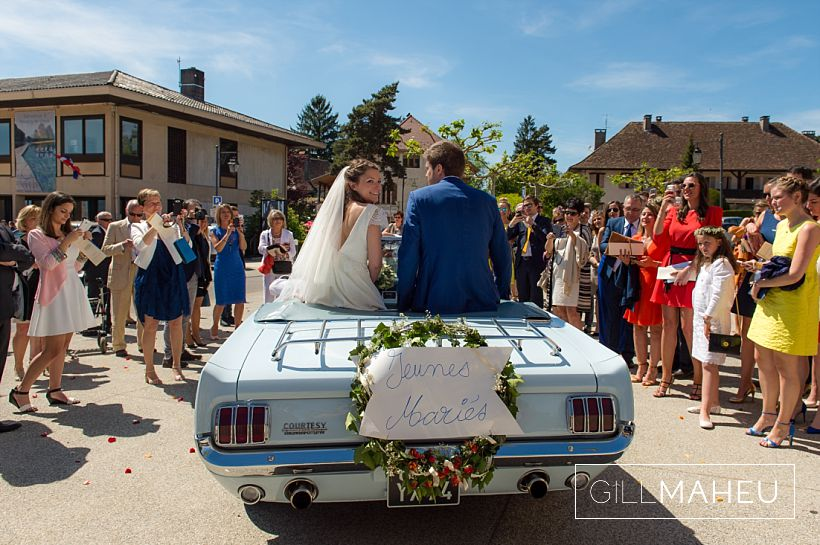 wedding couple sitting on the back of their wedding car mustang