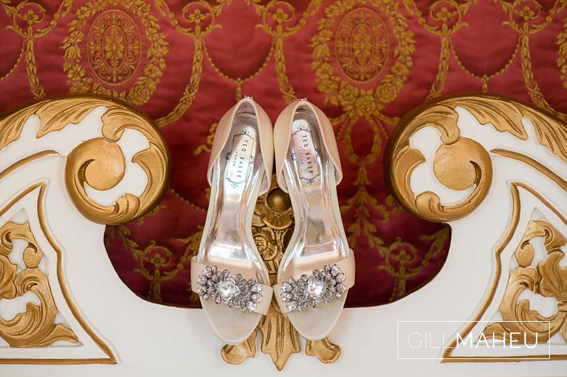 close up of luxurious wedding shoes on ornate gold detailed bed