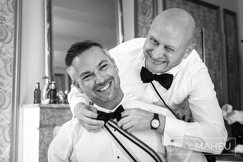 best man helping groom with bow tie before ceremony
