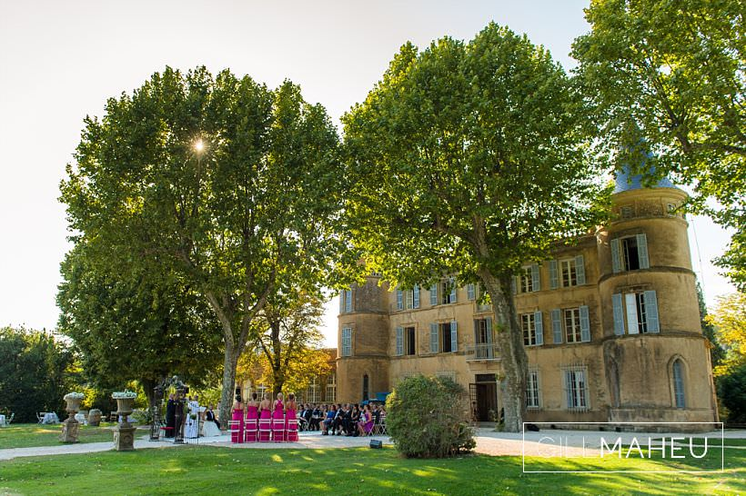 wide shot of a wedding ceremony with the chateau in provence as a backdrop