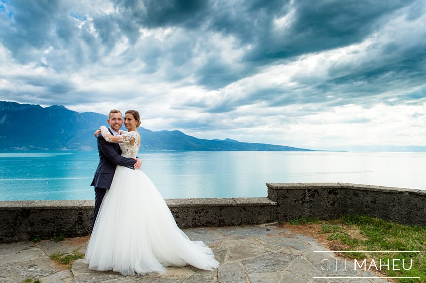 bride and groom with stormy skies over lake geneva