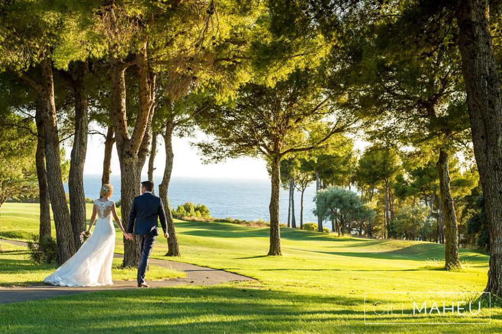 bride and groom wandering through the trees in the golden hour
