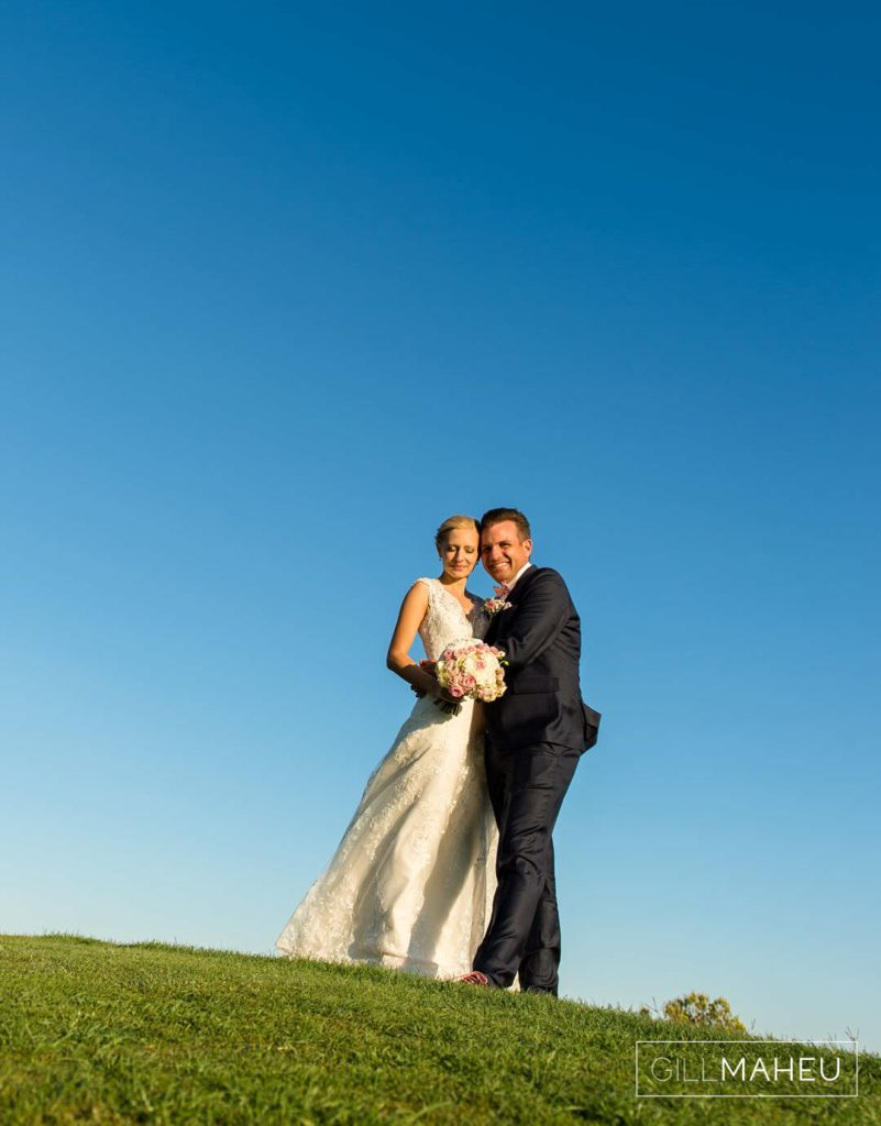 bride and groom with a clear blue sky