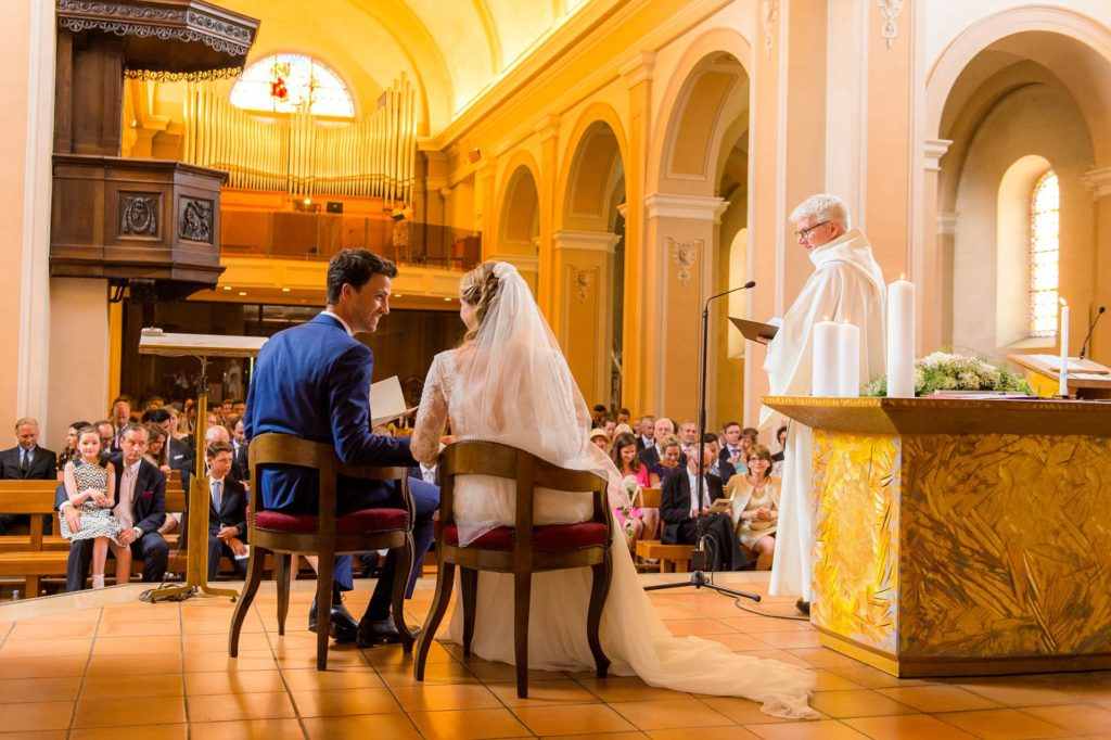 view of bride and groom and guest from behind the altar at annecy le vieux church