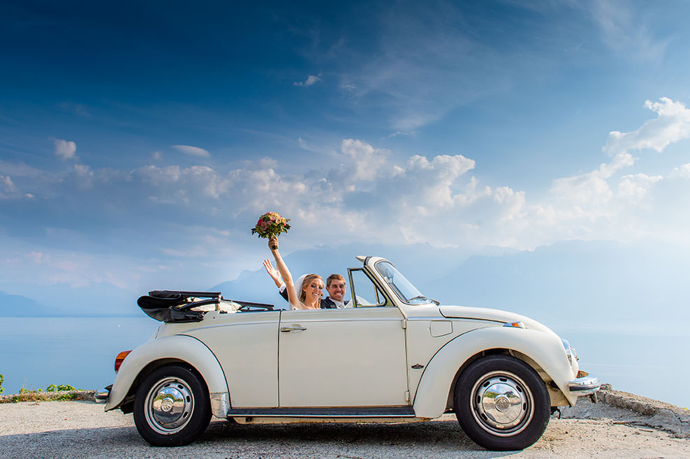 wedding portrait of bride and groom celebrating in white vw beetle in front of big blue sky by Gill Maheu Photography, photographe de mariage