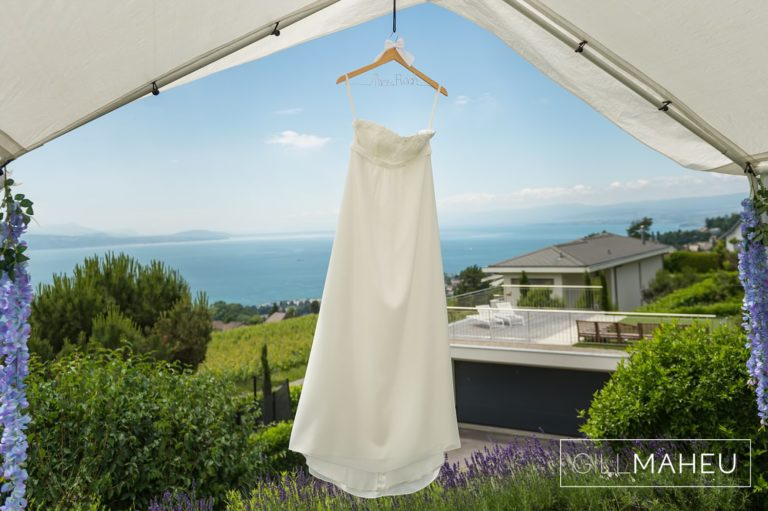 stunning Sweet Bella wedding dress hanging from tent in front of view of lac leman at Lutry, Lausanne wedding by Gill Maheu Photography, photographe de mariage