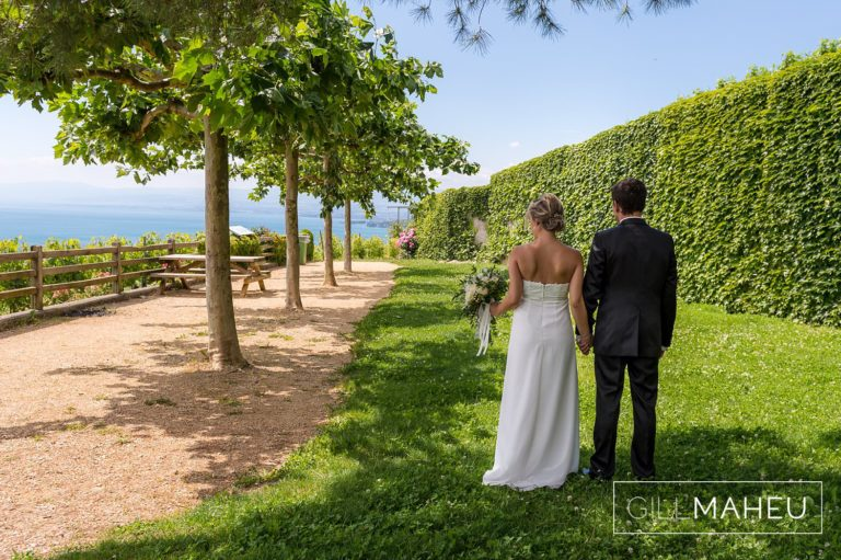 bride and groom walking away from camera at first look in park overlooking Lutry, Lausanne wedding by Gill Maheu Photography, photographe de mariage