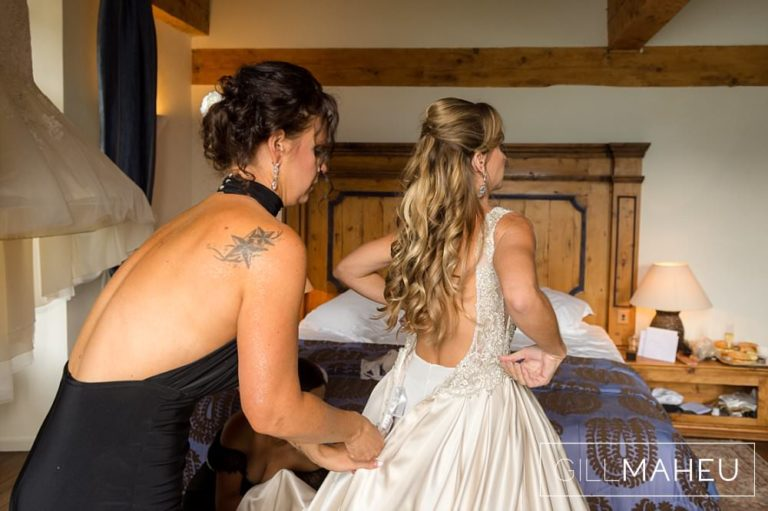bridesmaid helping bride into her wedding dress in the suite nuptiale Jean Reno at Abbaye de Talloires, Annecy wedding by Gill Maheu Photography, photographe de mariage