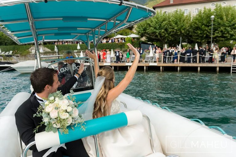 bride and groom waving back at their guests on the ponton jetty of the Abbaye de Talloires, Annecy wedding by Gill Maheu Photography, photographe de mariage