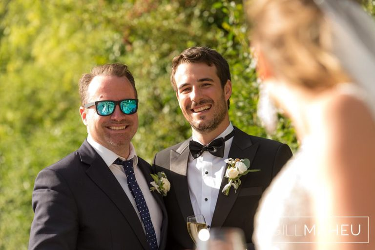 portrait of groom and brother smiling at the bride in the evening sunshine at Abbaye de Talloires, Annecy wedding by Gill Maheu Photography, photographe de mariage
