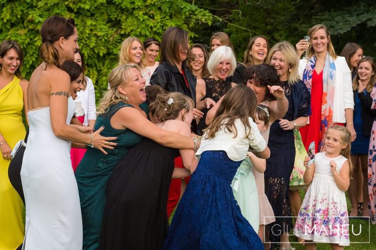 much laughter catching the bride's bouquet in the gardens of the Abbaye de Talloires, Annecy wedding by Gill Maheu Photography, photographe de mariage
