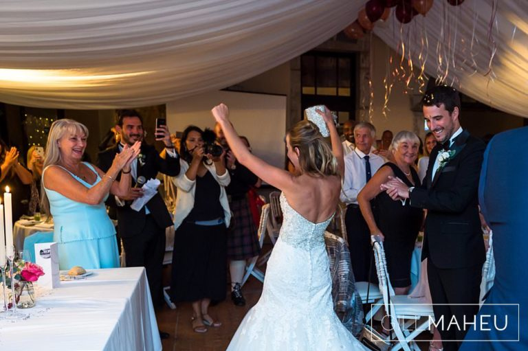 bride and groom make their joyous entrance to evening celebrations at Abbaye de Talloires, Annecy wedding by Gill Maheu Photography, photographe de mariage