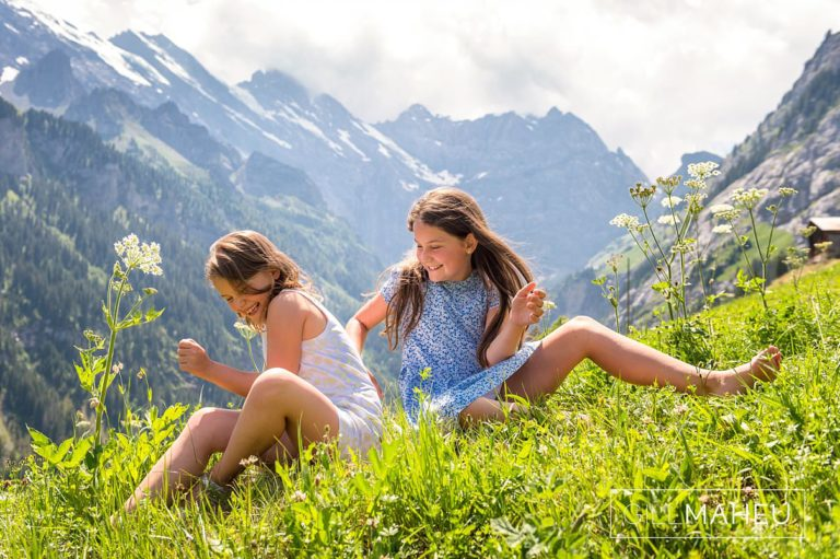 portrait of two sisters having a tickling fight in a flower field at summer sun lifestyle photography session in Gimmelwald a mountain village near Bern, Switzerland by Lifestyle photographer Gill Maheu Photography, photographe de famille