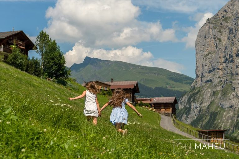 two young girls running through flower meadow in mountains at summer sun lifestyle photography session with beautiful young family in Gimmelwald, Switzerland by Lifestyle photographer Gill Maheu Photography, photographe de famille