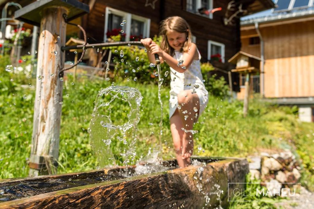 young girl balancing on ice cold water trough at summer sun lifestyle photography session in Gimmelwald a mountain village near Bern, Switzerland by Lifestyle photographer Gill Maheu Photography, photographe de famille